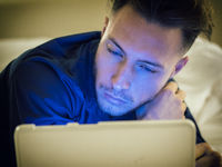 Handsome young man in bed typing on tablet PC
