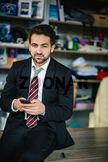 Successful businessman holds his phone and smiles