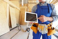 Construction worker pointing at tablet