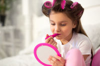 Cute girl putting on make up.