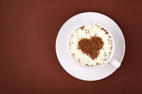 Full white cup of cappuccino coffee on brown
