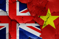 flags of UK and Vietnam painted on cracked wall