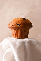 Blueberry Muffin on a pedestal draped with a kitchen towel