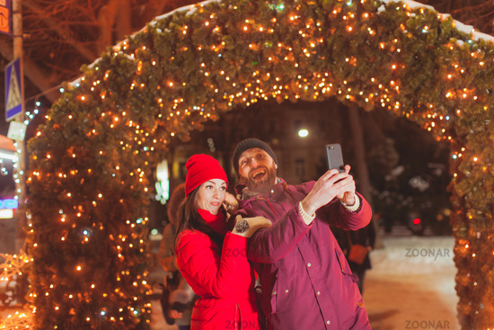 Couple making selfie near decorated arch with lights