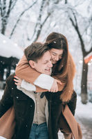 beautiful young couple having fun on a snowy street