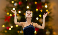 beautiful woman over christmas tree lights