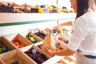 Woman is packing dried aprisots in the grocery shop