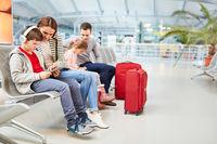 Familie mit Kindern im Flughafen Terminal muss warten