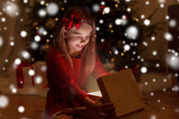smiling girl opening christmas gift at night