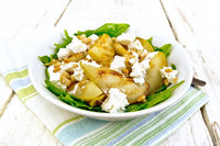Salad from pear and spinach in dish on light board