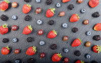 Flat lay view at ripe bilberry strawberry raspberry blackberry and gooseberry on slate stone tray closeup