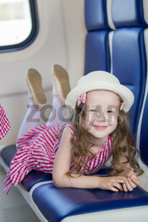 Cute smiling girl with long wavy hair in panama hat lying on armchair in the train