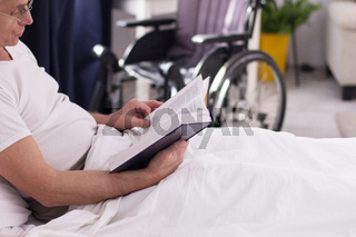 Disabled man reading in bed.