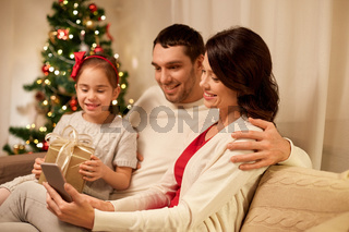 family with smartphone at home on christmas