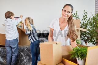 Junge Frau und Kinder beim Auspacken