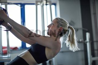 Frau beim Slingtraining als gesundes Rückentraining