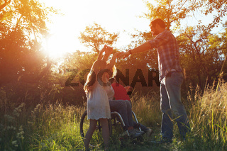 Woman in an armchair has fun with her husband and two children in park
