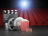 Cinema, movie or home video concept background. Film reels, clapper board  and pop corn in the theater movie cinema screen with empty seats.