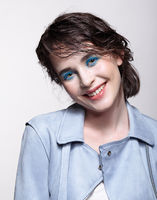 Portrait of smiling female in blue jacket. Woman with unusual beauty makeup and wet hair, and blue shadows make-up.