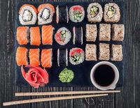 Various sushi rolls on slate