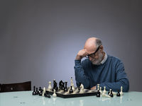 Senior man thinking over chess