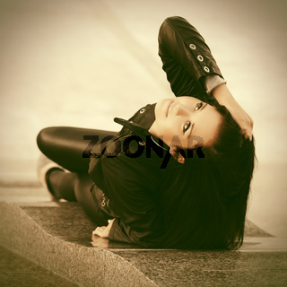Young fashion woman in leather jacket lying on sidewalk