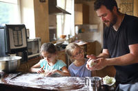 Children cooking homemade bread with there father