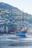 View of Bergen harbor in Norway with a sailing ship on its way to the sea