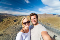 Active happy couple taking selfie on travel in high Atlas mountains, Ouarzazate, Morocco.