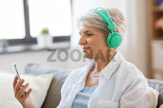 senior woman in headphones listening to music