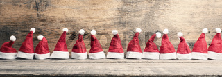 Hats of Santa in a row on wood
