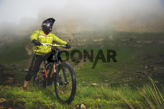 An adult mtb cyclist on a mountain bike at the foot of a cliff surrounded by green grass. Low clouds. North Caucasus. Russia