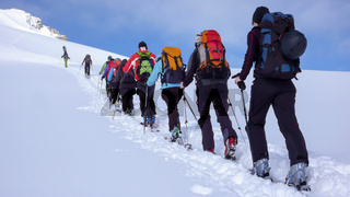 group of backcountry skiers crossing a glacier on their way to a high summit in the Alps