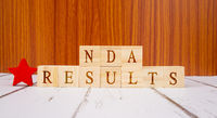 Concept of NDA exam conducted in India for recruitment, NDA Exam results on Wooden block letters.