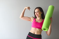 Attractive woman wearing pink sportswear holding green yoga or fitness mat after working out at home or in club