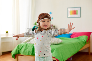 happy little girl in pilot hat playing at home