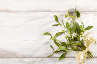 Branch of Mistletoe with ribbon on wooden background.