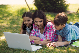 A teacher giving lesson with laptop in park