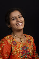 Portrait of a happy young Indian girl smiling on black background.