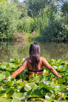 Colombian woman walking through water lilies