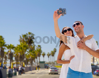 couple making selfie by camera over venice beach