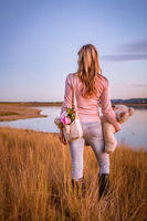 Woman standing in long dry grasses by lake