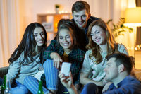friends with smartphone watching tv at home