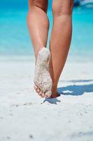 Woman walking on tropical white sand beach