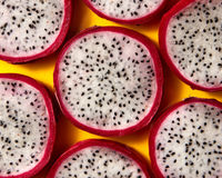 Close up view of background from round slices of Dragon fruit or Pitaya on a yellow background.