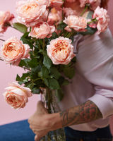 A large bouquet of fresh pink roses in a glass vase holds a girl statue on a pink background. Valentine's Day Gift