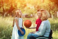 Pretty woman in wheelchair talks with children