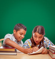 Blank Chalk Board Behind Hispanic Boy and Girl Having Fun Studying Together