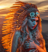 beautiful blonde with golden hair and sensual face with big american indian plume of brown feathers