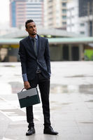 Young African businessman with briefcase thinking in the city outdoors